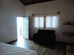 """Couch & Front Door– """"La Casa de Arbol"""" - Beach House Room - Treasure by The Sea Resort"""