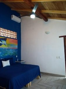 """Bed /nightstand – """"La Casa del Pez Vela"""" - Beach House Room - Treasure by The Sea Resort"""